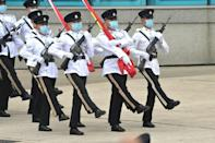 Hong Kong Police officers goose-step carrying the Chinese and Hong Kong flags during a flag-raising ceremony
