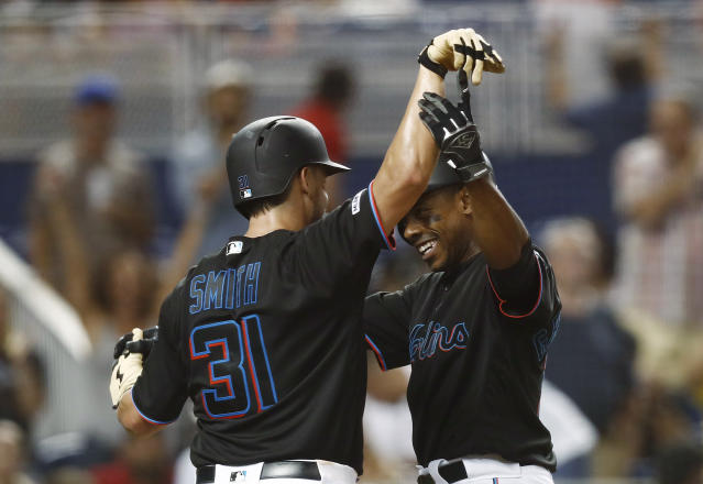 Miami Marlins' Curtis Granderson celebrates a two-run home run with Caleb Smith (31) during the third inning of the team's baseball game against the New York Mets on Friday, July 12, 2019, in Miami. (AP Photo/Brynn Anderson)