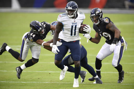 Tennessee Titans wide receiver A.J. Brown (11) runs with the ball as Baltimore Ravens cornerback Marlon Humphrey (44) and linebacker Chris Board (49) try to stop him during the second half of an NFL football game, Sunday, Nov. 22, 2020, in Baltimore. (AP Photo/Nick Wass)
