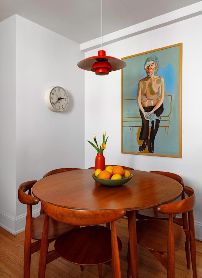 "<div class=""caption""> The dining area off of the kitchen is small, so Joey looked for a compact circular dining table to fit. A painting he made in high school hangs above it. </div>"