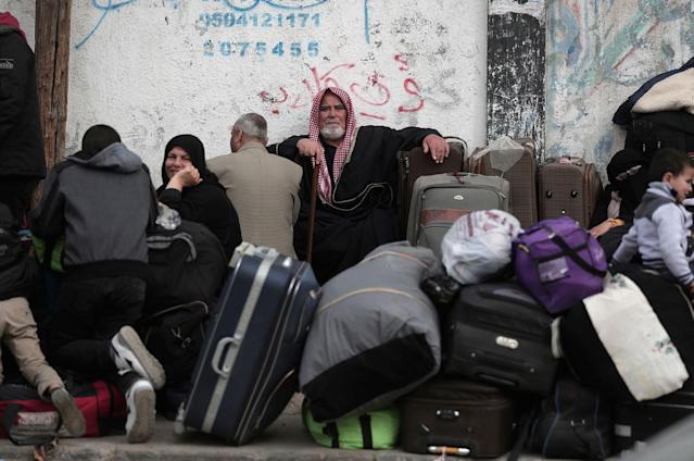 <p>Palestinians sit with their luggage as they wait to enter the Rafah border crossing with Egypt, in the southern Gaza Strip, Thursday, Feb, 8, 2018. (Photo: Khalil Hamra/AP) </p>