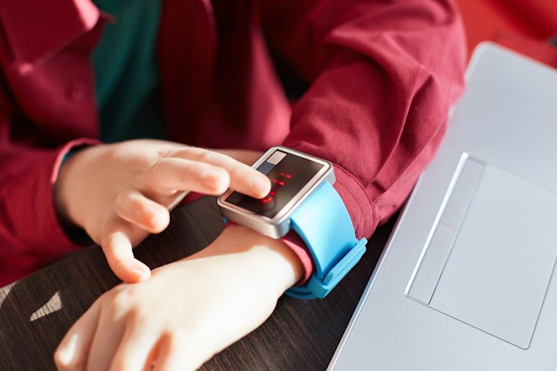 A close-up of child`s hands with smart watch. Touching electronic watch. Wearable gadget concept. Showing time. Using smartwatch while sitting near the laptop. Technology and people concept.