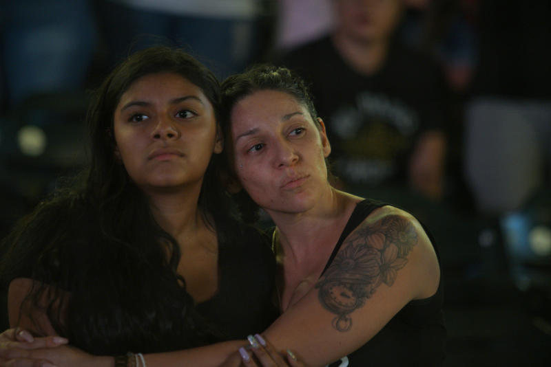 """Mourners listen to """"Amor Eterno"""" performed by mariachis during a community memorial service, Wednesday, Aug. 14, 2019, at Southwest University Park, in El Paso, Texas, for the people killed in a mass shooting on Aug. 3. (AP Photo/Jorge Salgado)"""