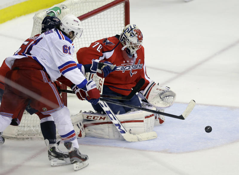 New York Rangers left wing Rick Nash (61) shoots and has his shot blocked by Washington Capitals goalie Braden Holtby (70) in the second period of Game 1 of a Stanley Cup NHL playoff hockey series on Thursday, May 2, 2013, in Washington. The Capitals won 3-1. (AP Photo/Alex Brandon)