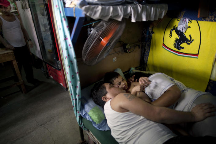 In this May 2, 2012 photo, inmate Denis Castillo cuddles with his wife, Reina Lopez, and their son Dermin Valentin during visiting hours at the San Pedro Sula Central Corrections Facility in San Pedro Sula, Honduras. Inside one of Honduras' most dangerous and overcrowded prisons, inmates operate a free-market bazaar, selling everything from iPhones to prostitutes. Guards do not cross into the inner sanctum controlled by prisoners, and prisoners do not breach the perimeter controlled by guards. (AP Photo/Rodrigo Abd)