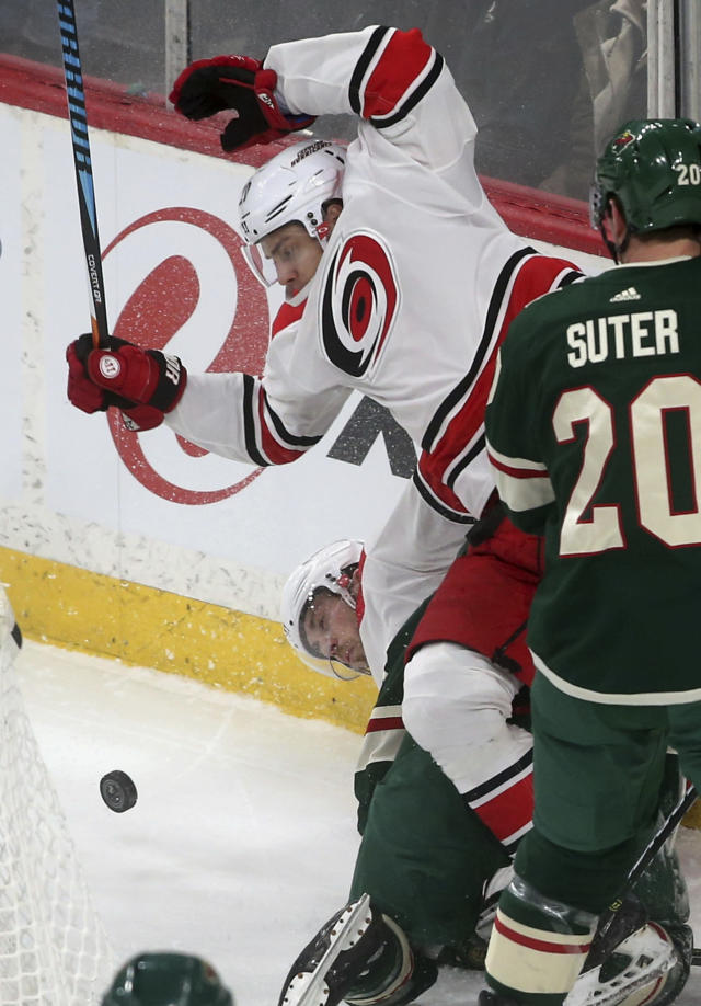 Carolina Hurricanes' Elias Lindholm, left, of Sweden, tumbles over Minnesota Wild's Jared Spurgeon and a Hurricanes teammate during the first period of an NHL hockey game Tuesday, March 6, 2018, in St. Paul, Minn. (AP Photo/Jim Mone)