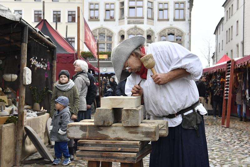 A traditional wood cutter engraves wood in the main square in Wittenberg, eastern Germany, where celebrations take place on the occasion of the 500th anniversary of the Reformation on October 31, 2017.  (JOHN MACDOUGALL via Getty Images)