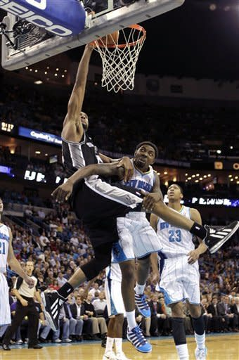 San Antonio Spurs power forward Tim Duncan goes to the basket against New Orleans Hornets shooting guard Roger Mason Jr., right, in the second half of an NBA basketball game in New Orleans, Wednesday, Oct. 31, 2012. The Spurs won 95-99. (AP Photo/Gerald Herbert)