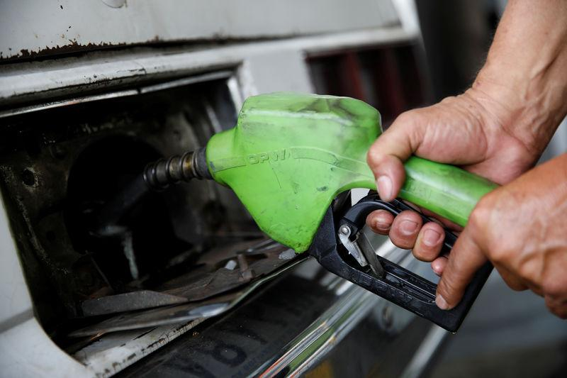 A gas station worker pumps gas into a car at a gas station of the state oil company PDVSA in Caracas