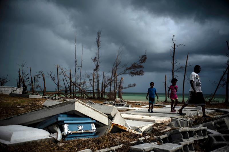 People walk next to a shattered and water-filled coffin lays exposed to the elements in the aftermath of Hurricane Dorian, at the cemetery in Mclean's Town, Grand Bahama, Bahamas, Friday Sept. 13, 2019.