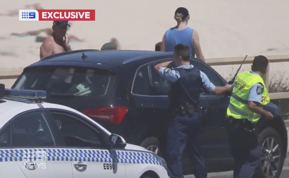 NSW Police smash the window of a car after a baby became trapped inside at Maroubra Beach.