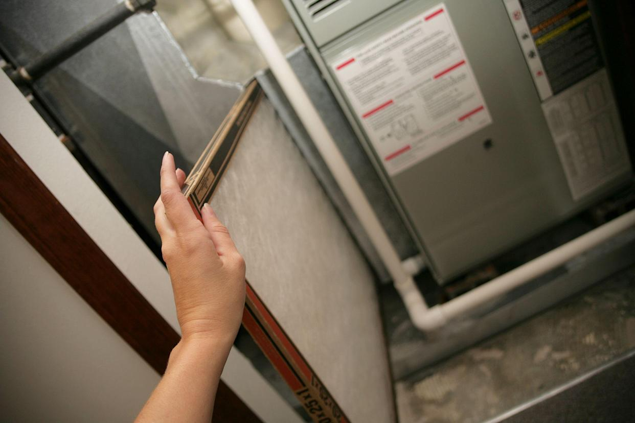 hand on furnace changing air filters