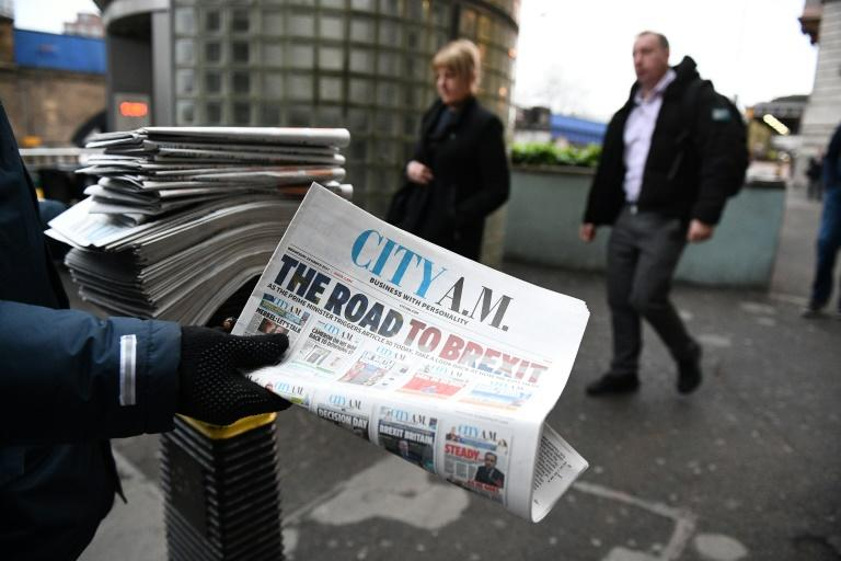 A man hands out copies of the City A.M. newspaper outside Waterloo station in central London on March 29, 2017