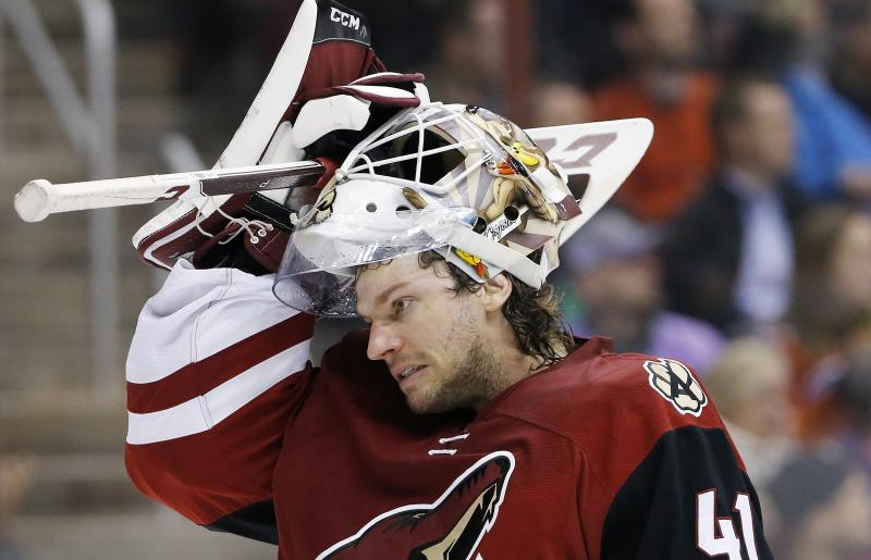 This March 22, 2016 photo shows Arizona Coyotes' Mike Smith putting his mask back on as he skates back to his position during the first period of an NHL hockey game against the Edmonton Oilers in Glendale, Ariz. When a collision knocked Smith's mask off, the Arizona Coyotes goaltender was less than pleased when he was told a few minutes later he had no choice but to leave the game. NHL general managers expected to talk about video review and concussion protocol for goaltenders at their annual March meeting. Coach's challenges for offside and goaltender interference will be on the docket at the GMs meeting in Boca Raton, Florida, this week. (AP Photo/Ross D. Franklin)