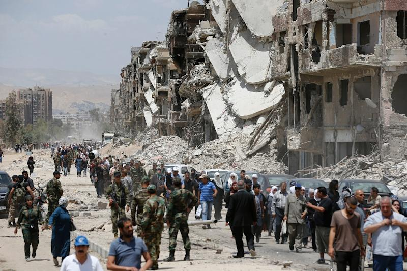 Civilians and pro-government forces walk down the destroyed Thalateen Street in the Yarmuk Palestinian refugee camp on the southern outskirts of the Syrian capital Damascus on May 24, 2018, after the regime seized the camp