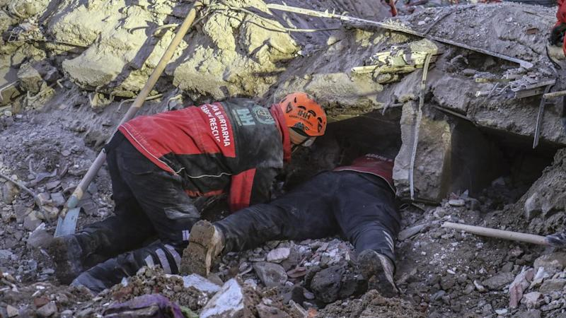 Rescue workers search for people trapped under debris after a strong earthquake in Turkey's east