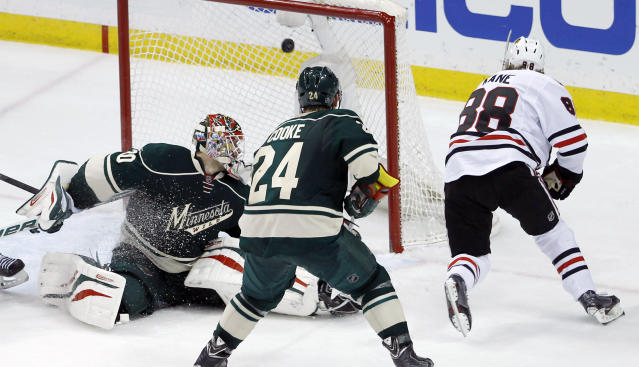 The game-winning shot by Chicago Blackhawks right wing Patrick Kane (88) gets past Minnesota Wild goalie Ilya Bryzgalov, left, of Russia, in front of Wild left wing Matt Cooke (24) during overtime of Game 6 of an NHL hockey second-round playoff series in St. Paul, Minn., Tuesday, May 13, 2014. The Blackhawks won 2-1. (AP Photo/Ann Heisenfelt)