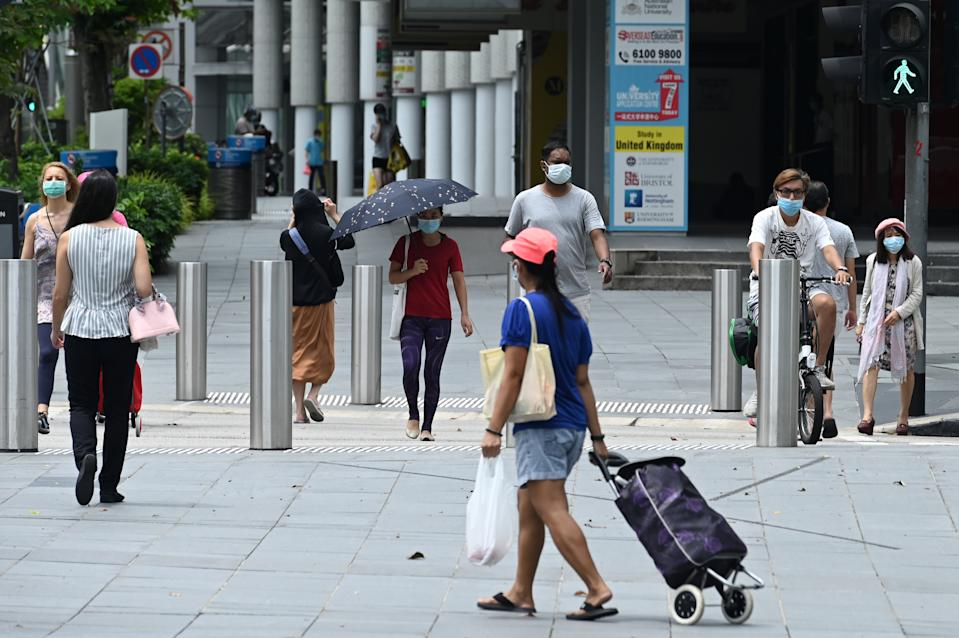 People, wearing face masks as a preventive measure against the spread of the COVID-19 novel coronavirus, cross a road along the Orchard Road shopping belt in Singapore on May 6, 2020. (Photo by Roslan RAHMAN / AFP) (Photo by ROSLAN RAHMAN/AFP via Getty Images)