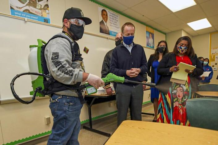Panorama City, CA - March 10: Plant manager Sergio Ruiz, left, in presence of Superintendent Austin Beutner , center, and UTLA President Cecily Myart-Cruz demonstrates the use of a electrostatic sprayer to disinfect a classroom at Panorama High School on Wednesday, March 10, 2021 in Panorama City, CA.(Irfan Khan / Los Angeles Times)