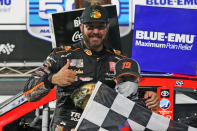 Martin Truex Jr. gives a thumbs-up as he celebrates with a fan after winning a NASCAR Cup Series auto race at Martinsville Speedway in Martinsville, Va., Sunday, April 11, 2021. (AP Photo/Steve Helber)