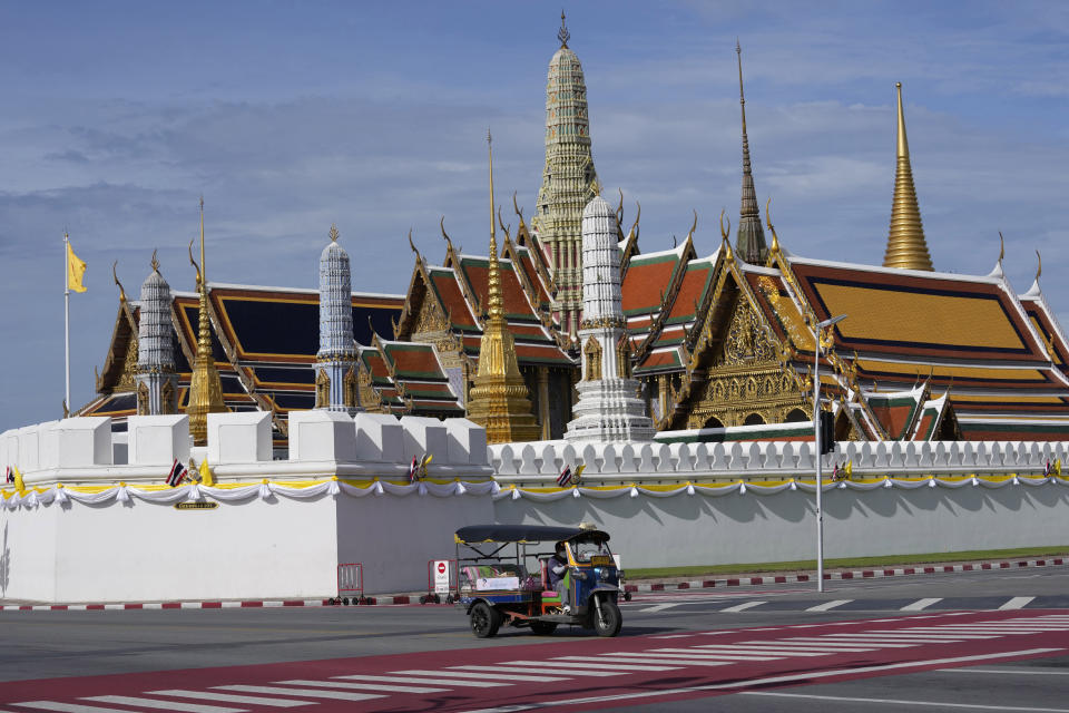 A motor-tricycle, or Tuk Tuk drives past Grand Palace in Bangkok, Thailand on Aug. 3, 2021. As Thailand battles a punishing COVID-19 surge with nearly 20,000 new cases every day, people who depend on tourism struggle in what was one of the most-visited cities in the world, with 20 million visitors in the year before the pandemic. (AP Photo/Sakchai Lalit)