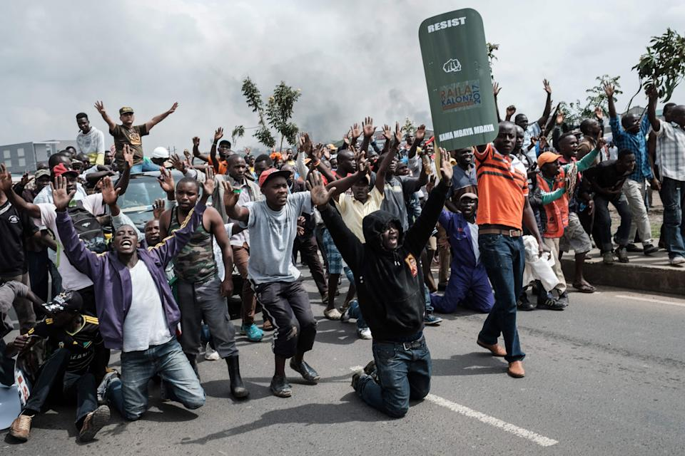 <p>Supporters of Kenyan's opposition party National Super Alliance (NASA) react when confronted by Kenyan police, as they attempt to march towards the Jomo Kenyatta international airport to welcome opposition leader Raila Odinga upon his arrival on Nov. 17, 2017 in Nairobi. (Photo: Yasuyoshi Chiba/AFP/Getty Images) </p>