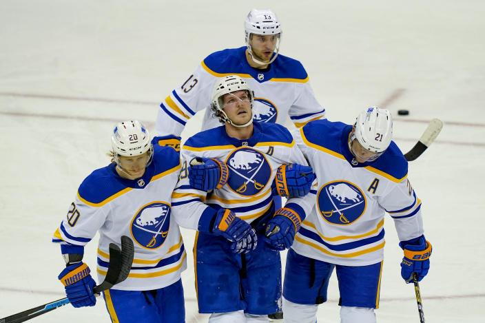 Buffalo Sabres defenseman Jake McCabe (19) reacts after taking an injury and being helped off the ice during the third period of an NHL hockey game against the New Jersey Devils, Saturday, Feb. 20, 2021, in Newark, N.J. (AP Photo/John Minchillo)