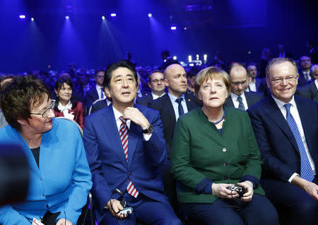 German Chancellor Angela Merkel and Japanese Prime Minister Shinzo Abe attend the opening ceremony of the CeBit computer fair, which will open its doors to the public on March 20, at the fairground in Hanover, Germany, March 19, 2017.     REUTERS/Morris Mac Matzen
