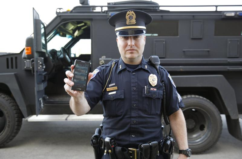 <p> In a May 6, 2014 photo, Sgt. Andres Wells of the Kalamazoo Dept. of Public Safety, who successfully used text messaging to negotiate with a suicidal robbery suspect during a 2011 standoff, stands next to his armored vehicle. With 6 billion text messages exchanged daily in the United States, texting is becoming a more frequent part of police crisis negotiations. (AP Photo/Mark Bugnaski) </p>