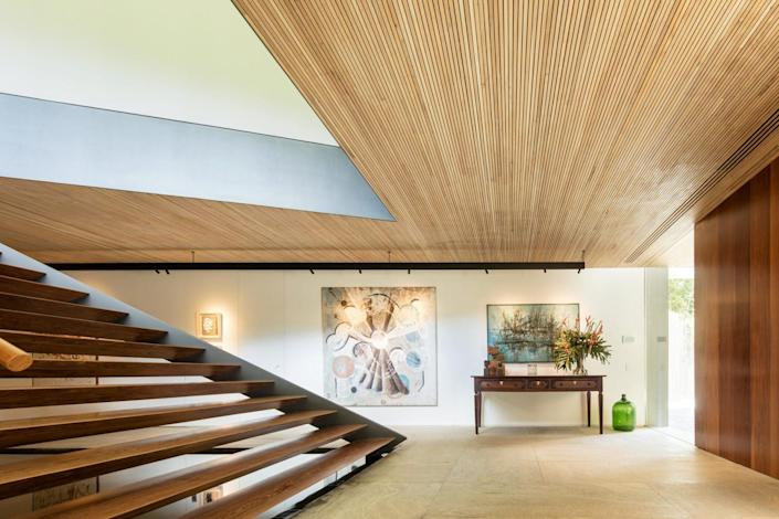 Spacious foyer/entryway inside the Bernardes Arquitetura-designed Asa House, adorned with timber slats in the ceiling and granite floors.