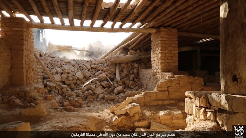 An image published by the media branch of the Islamic State group in the Damascus province (Welayat Dimashq) on August 21, 2015, allegedly shows IS jihadists using a bulldozer to destroy the ancient Syriac Catholic monastry of Mar Elian (AFP Photo/-)