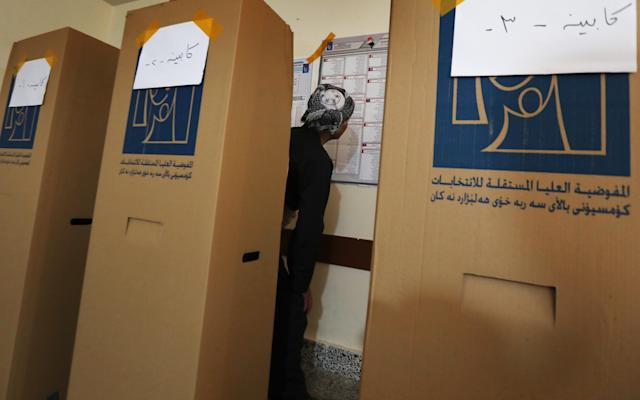 <p>An Iraqi Kurdish man dressed in traditional costume looks at the names on the electoral lists hung behind him before ticking his ballot behind a voting booth at a polling station in Arbil, the capital of the Kurdish autonomous region in northern Iraq, on May 12, 2018 as the country votes in the first parliamentary election since declaring victory over the Islamic State (IS) group. (Photo: Safin Hamed/AFP/Getty Images) </p>