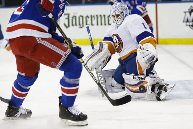 New York Islanders goaltender Thomas Greiss stops a shot on goal by New York Rangers' Brett Howden, left, during the second period of an NHL hockey game Tuesday, Jan. 21, 2020, in New York. (AP Photo/Frank Franklin II)