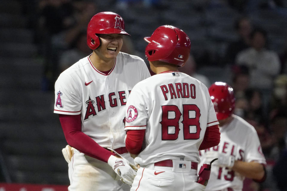 Los Angeles Angels designated hitter Shohei Ohtani, right, laughs at the bat boy after being intentionally walked during the ninth inning of a baseball game against the Seattle Mariners Friday, Sept. 24, 2021, in Anaheim, Calif. (AP Photo/Mark J. Terrill)