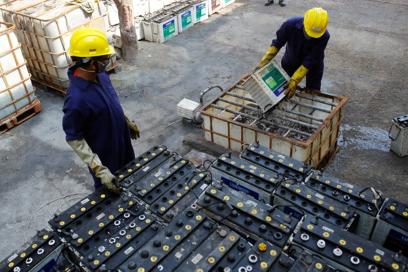 Workers dismantle batteries to obtain lead from them at ACE Green recycling Inc in Ghaziabad