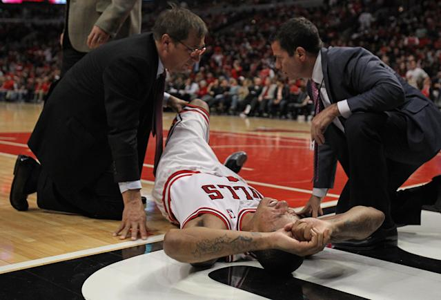 CHICAGO, IL - APRIL 28: Derrick Rose #1 of the Chicago Bulls is examined after suffering an injury against the Philadelphia 76ers in Game One of the Eastern Conference Quarterfinals during the 2012 NBA Playoffs at the United Center on April 28, 2012 in Chicago, Illinois. The Bulls defeated the 76ers 103-91. NOTE TO USER: User expressly acknowledges and agrees that, by downloading and or using this photograph, User is consenting to the terms and conditions of the Getty Images License Agreement. (Photo by Jonathan Daniel/Getty Images)