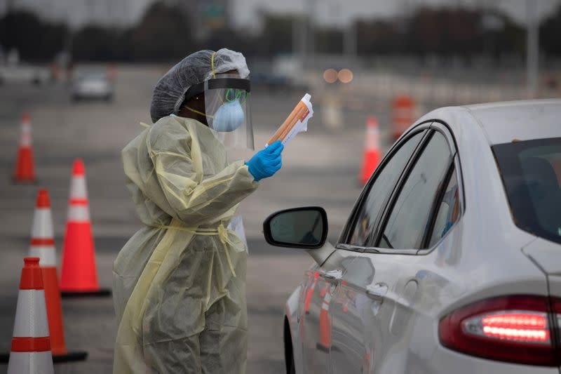 A healthcare worker holds a coronavirus disease (COVID-19) informational pamphlet for a resident at a drive-thru testing location in Houston