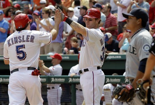 Texas Rangers' Ian Kinsler, left, is greeted by teammate Josh Hamilton, center, at home after scoring on a Michael Young single off a pitch from Seattle Mariners relief pitcher Erasmo Ramirez, right, in the seventh inning of a baseball game on Thursday, April 12, 2012, in Arlington, Texas. The Rangers won 5-3. (AP Photo/Tony Gutierrez)