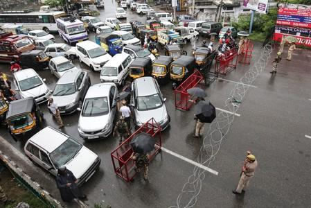 Indian security personnel stand guard as they stop traffic during restrictions in Jammu