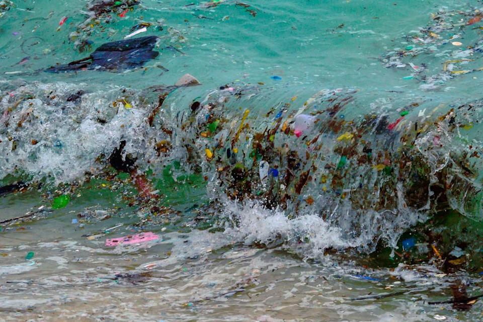 A wave carrying plastic waste and other rubbish washes up on a beach in Koh Samui in the Gulf of Thailand.