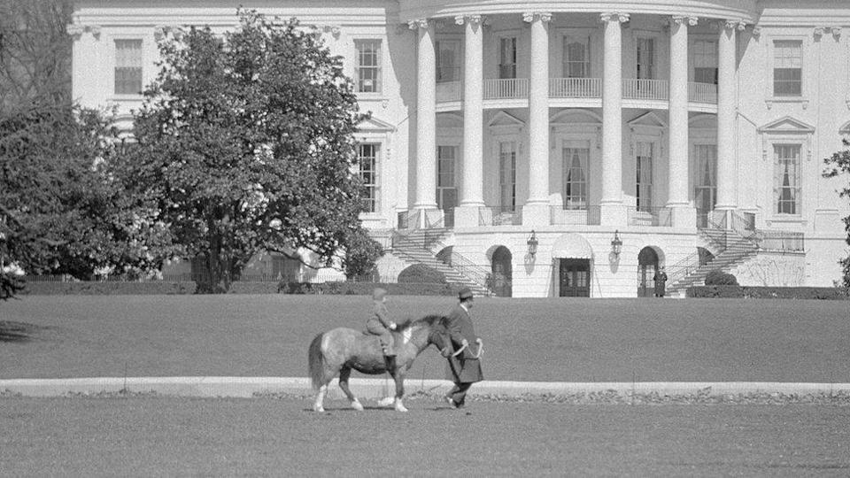 With a Secret Service man leading the way, Caroline Kennedy, the President`s daughter, takes a ride on her pony, Macaroni, in 1962