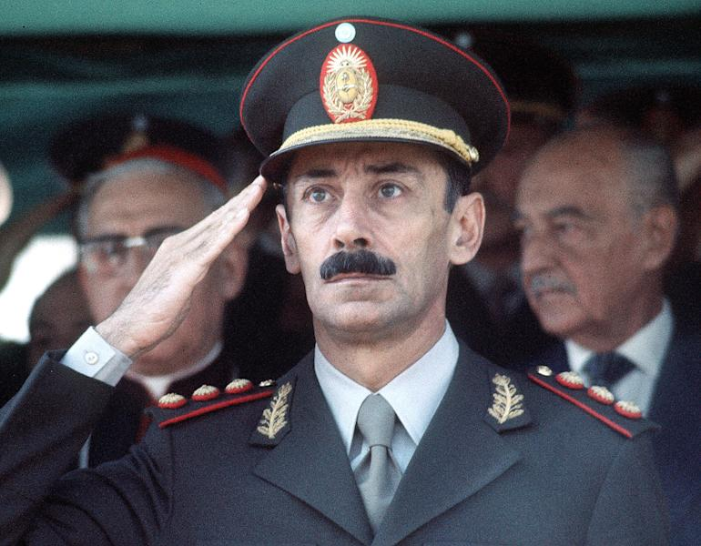 """FILE - In this March 24, 1977 file photo, Gen. Jorge Rafael Videla is seen commemorating the first anniversary of the military coup in Asuncion, Argentina. The former Argentine dictator died of natural causes Friday, May 17, 2013, while serving life sentences at the Marcos Paz prison for crimes against humanity. Videla took power in a 1976 coup and led a military junta that killed thousands of his fellow citizens in a dirty war to eliminate """"subversives."""" He was 87. (AP Photo/Eduardo Di Baia, File)"""