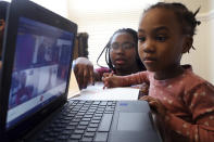 Lear Preston, 4, who attends Scott Joplin Elementary School, participates in her virtual classes as her mother, Brittany Preston, background, assists at their residence in Chicago's South Side, Wednesday, Feb. 10, 2021. Starting Thursday, Lear will return to class as the nation's third-largest school district slowly reopens its doors following a bitter fight with the teachers union over COVID-19 safety protocols. (AP Photo/Shafkat Anowar)