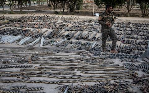 An SDF fighter looks over seized Isil weapons that were found in the last stronghold of the extremist group as they were displayed at an SDF base - Credit: Getty
