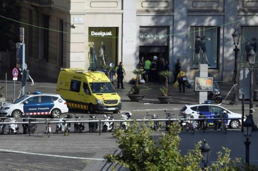 Police and medical staff stand in the entrance of a mall after a deadly attack when a van ploughed into the crowd on Las Ramblas boulevard in Barcelona on  August 17, 2017
