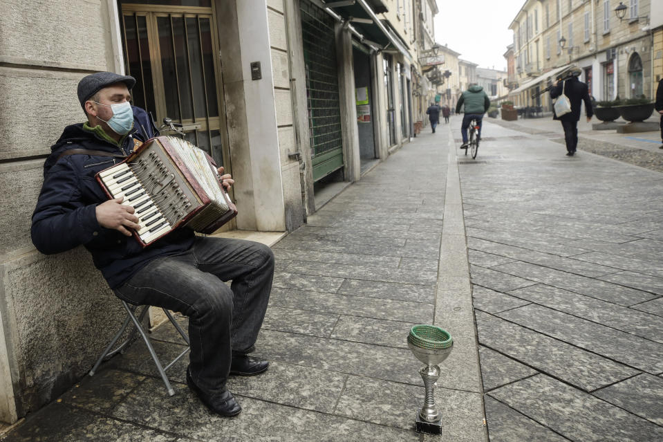 A man plays an accordion in Codogno, northern Italy, Sunday, Feb. 21, 2021. The first case of locally spread COVID-19 in Europe was found in the small town of Codogno, Italy one year ago on February 21st, 2020. With wreath-laying ceremonies, tree plantings and church services, Italians on Sunday marked the passing of one year since their country experienced the first known COVID-19 locally spread cases in the West. (AP Photo/Luca Bruno)
