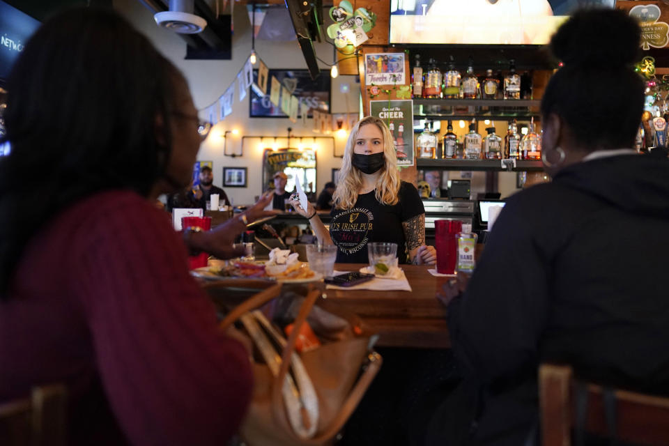FILE - In this March 10, 2021, file photo, bartender Angie Gibson, center, waits on Monica Ponton, left, and Devona Williams, right, at Mo's Irish Pub in Houston. Optimism is spreading in the U.S. as COVID-19 deaths plummet and states ease restrictions and open vaccinations to younger adults. But across Europe, dread is setting in with another wave of infections that is closing schools and cafes and bringing new lockdowns. (AP Photo/David J. Phillip, File)