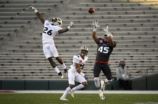 National team's Marcus Baugh, right, of Ohio State, catches a pass as American team's Rico Gafford, left, of Wyoming, and Ezekiel Turner, of Washington, defend during the second half of the Collegiate Bowl college football game, Saturday, Jan. 20, 2018, in Pasadena, Calif. The National team won 23-0. (AP Photo/Mark J. Terrill)