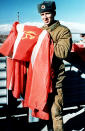FILE - In this Jan. 24, 1989 file photo, a Soviet army soldier takes down the Soviet national flag at Kabul airbase. The former Soviet Union marched into Afghanistan on Christmas Eve, 1979, claiming it was invited by the new Afghan communist leader, Babrak Karmal, setting the country on a path of 40 years of seemingly endless wars and conflict. After the Soviets left in humiliation, America was the next great power to wade in. (AP-Photo/Liu Heung-Shing)