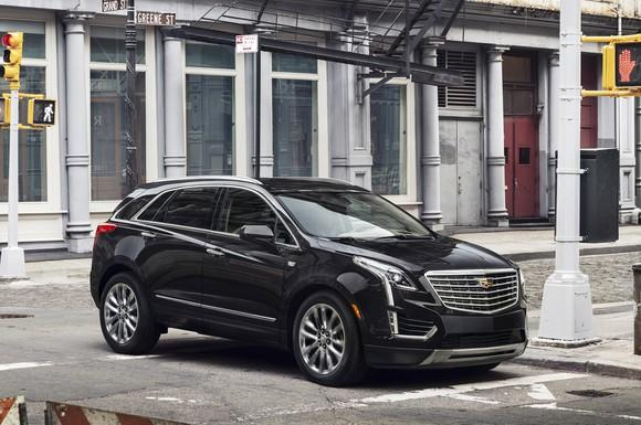 A black Cadillac XT5, a midsize crossover SUV, on a city street.